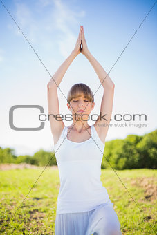 Peaceful young woman exercising outside