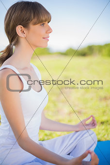 Smiling young woman meditating in lotus position