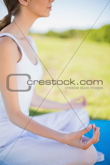 Peaceful young woman sitting in yoga position on her mat
