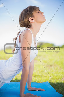 Natural young woman stretching on her mat