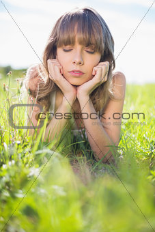 Thoughtful young woman lying on the grass