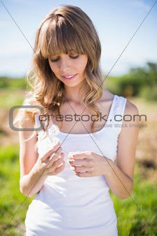 Pretty young woman holding dandelion