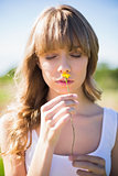 Pensive young woman smelling flower