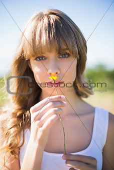 Pretty young woman smelling yellow flower