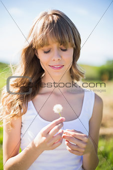 Relaxed young woman holding dandelion