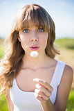 Pretty young woman blowing on dandelion