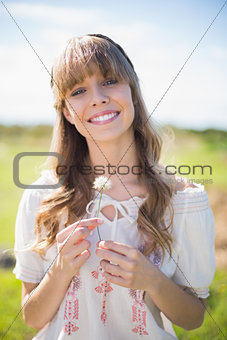 Cheerful young woman holding dandelion