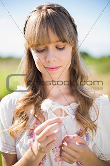 Peaceful young woman admiring dandelion