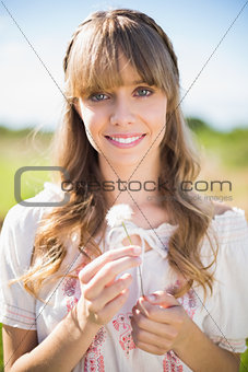 Smiling young woman admiring dandelion