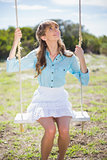 Smiling young model relaxing while sitting on swing