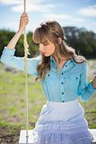 Pretty young model relaxing sitting on swing