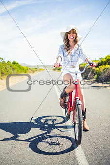 Smiling pretty model posing while riding bike