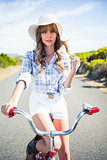 Trendy young woman posing while riding bike
