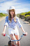 Mysterious young woman posing while riding bike