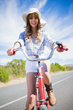 Smiling trendy woman posing while riding bike