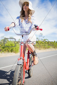 Thoughtful young woman posing while riding bike