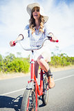 Cheerful trendy woman posing while riding bike