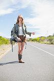 Natural blonde woman posing while hitchhiking