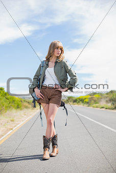 Thoughtful sexy blonde posing while hitchhiking
