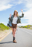Sexy blonde making gesture while hitchhiking