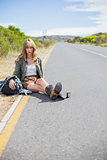 Tired blonde woman sitting on the roadside