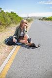 Pensive blonde woman sitting on the roadside
