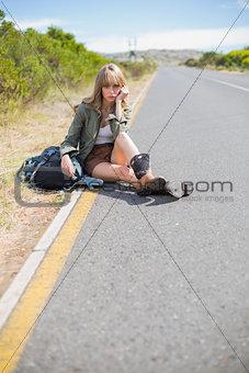 Tired pretty blonde sitting on the roadside