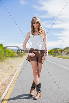 Attractive woman posing while hitchhiking