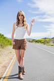 Gorgeous woman making gesture while hitchhiking