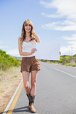 Smiling woman holding sign while hitchhiking