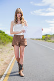 Cheerful woman holding sign while hitchhiking