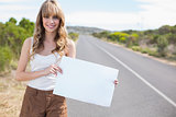 Smiling pretty woman holding sign while hitchhiking