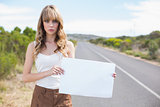 Serious pretty woman holding sign while hitchhiking