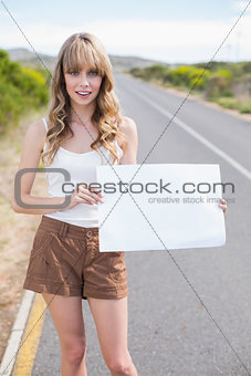 Attractive blonde holding sign while hitchhiking