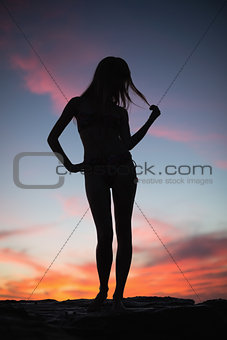 Silhouette of attractive woman posing on the beach