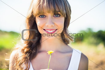 Smiling natural blonde holding dandelion