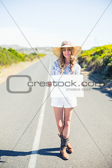 Smiling blonde holding sign while hitchhiking on the road