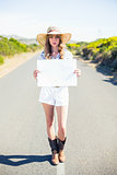 Serious blonde holding sign while hitchhiking on the road