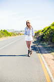 Trendy blonde with sunglasses hitchhiking