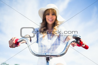 Cheerful trendy blonde riding her bike