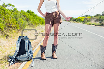 Backpacking woman on the roadside thumbs up posing