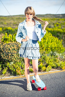 Trendy blonde skater posing on the roadside