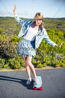 Attractive blonde balancing on her skateboard