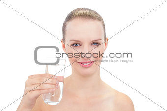 Amused pretty blonde model holding a glass of water