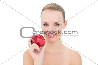 Amused pretty blonde model holding an apple