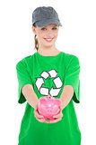 Natural pretty environmental activist offering a piggy bank