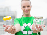 Pleased pretty environmental activist offering two jars