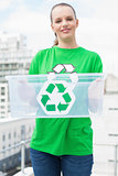 Pleased pretty environmental activist holding a recycling box