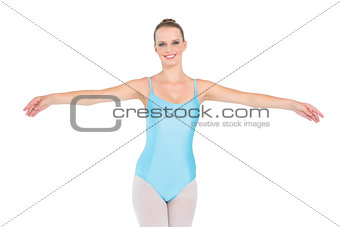 Cheerful pretty ballerina posing raising her arms