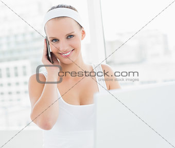 Smiling pretty sportswoman answering a phone call